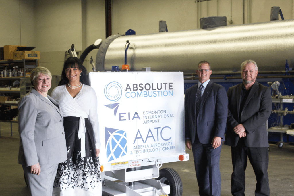 Laura Kilcrease, CEO of Alberta Innovates, Koleya Karringten, CEO of Absolute Combustion International, Steve Maybee, VP of Operations and Infrastructure, Edmonton International Airport and Rollie Dykstra, VP of Investments, Alberta Innovates, pose in front of the new Absolute Combustion International-SM1000 portable aircraft heater, tested and produced in Alberta.