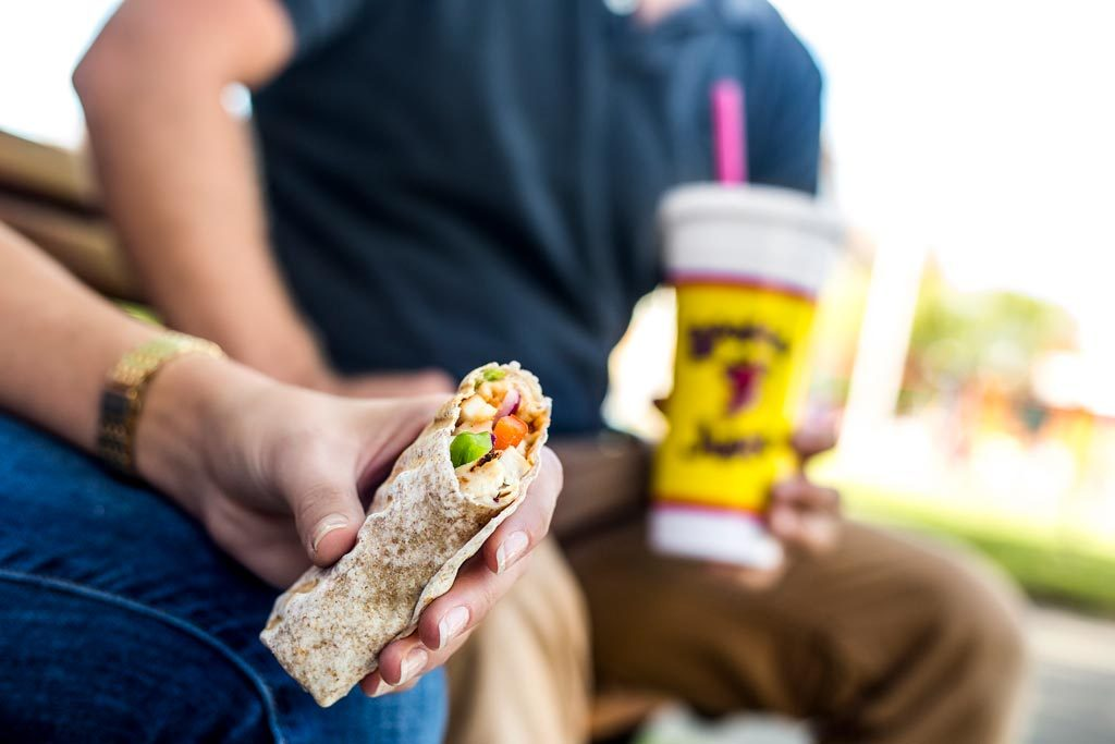 Photo of two customers enjoying a wrap and smoothie from Booster Juice