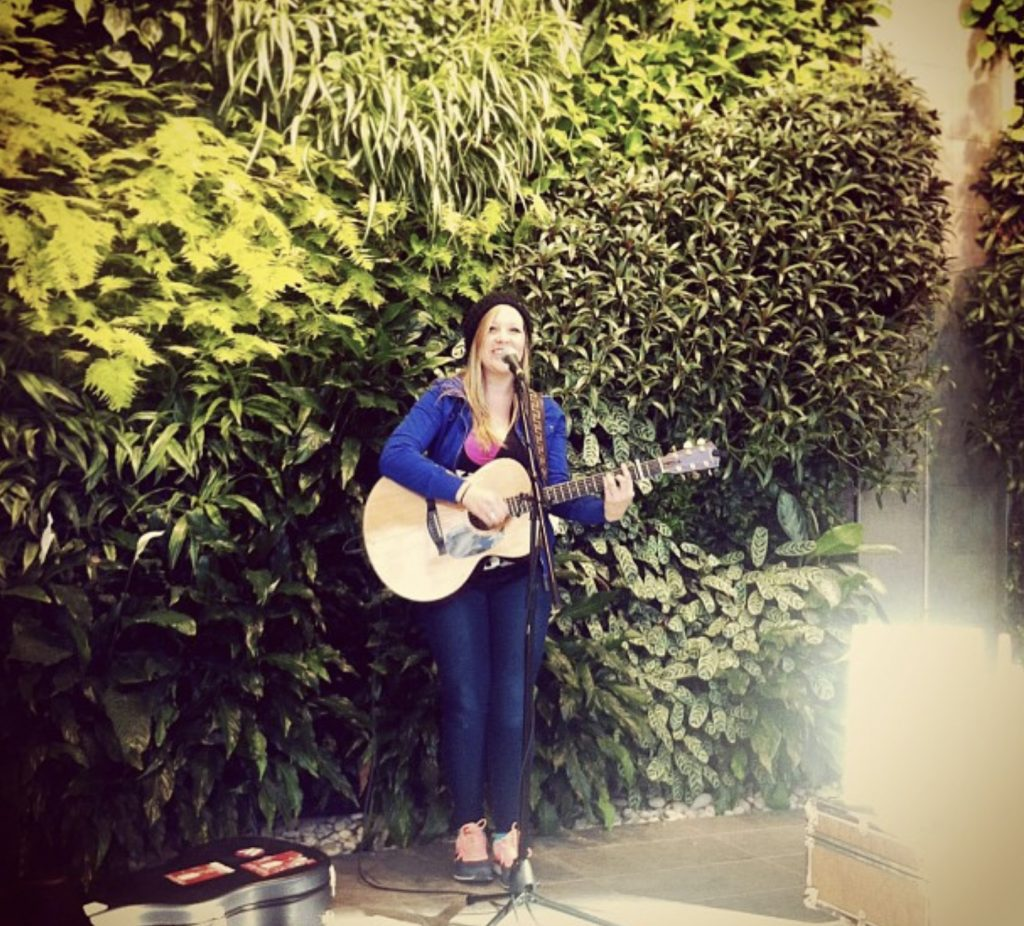 Young woman playing her guitar and signing in front of the Living Wall Artwork