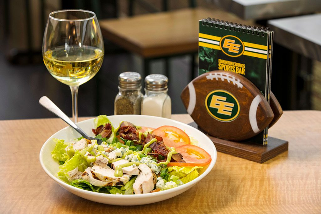 Photograph of Chicken Caesar Salad, wine and drink menus at Edmonton Eskimos Sports Bar