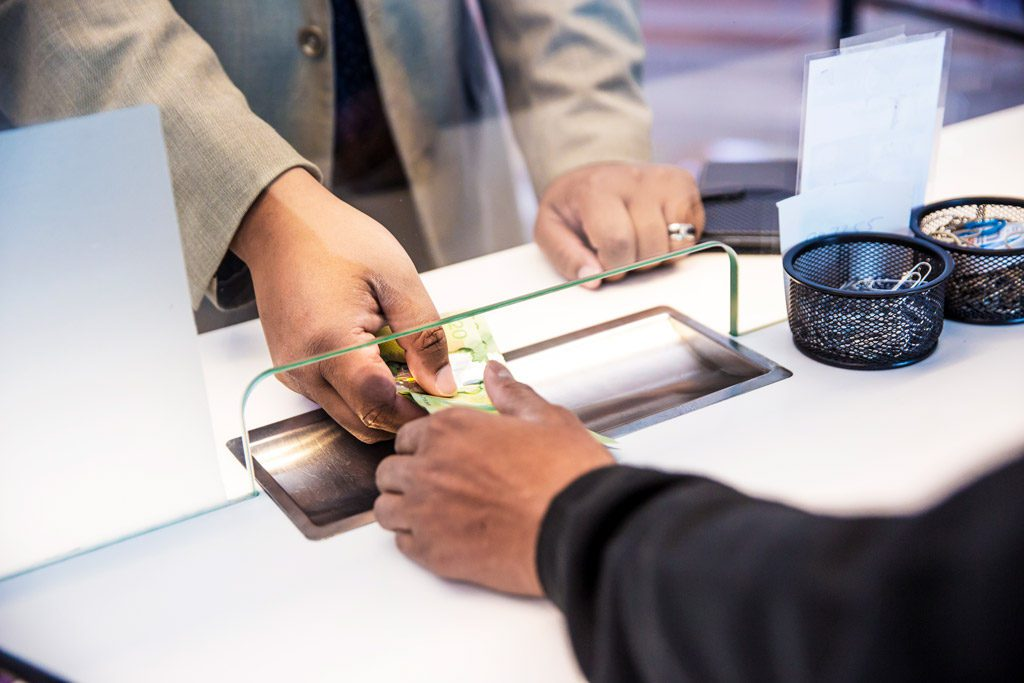 Photo d'un client échangeant des devises avec un préposé à travers une vitre de protection - International Currency Exchange