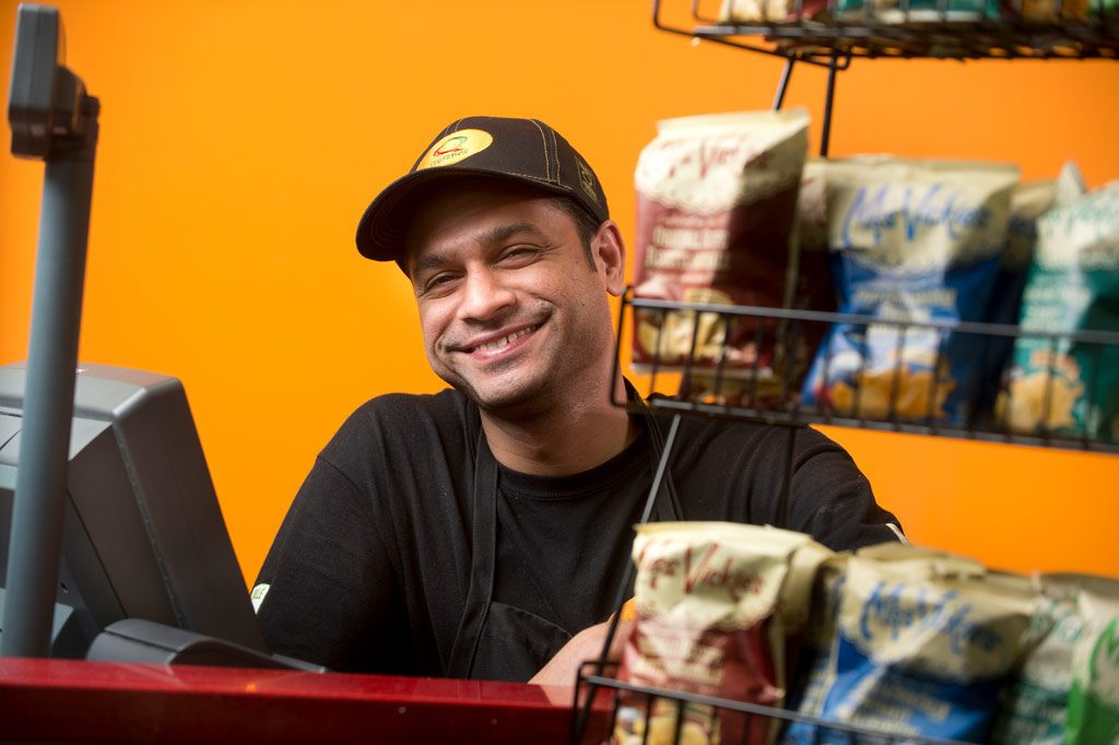 Photograph of Quiznos employee smiling at checkout