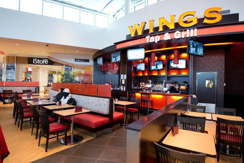Photograph of Wings Tap & Grill Bar + Storefront and restaraunt seating
