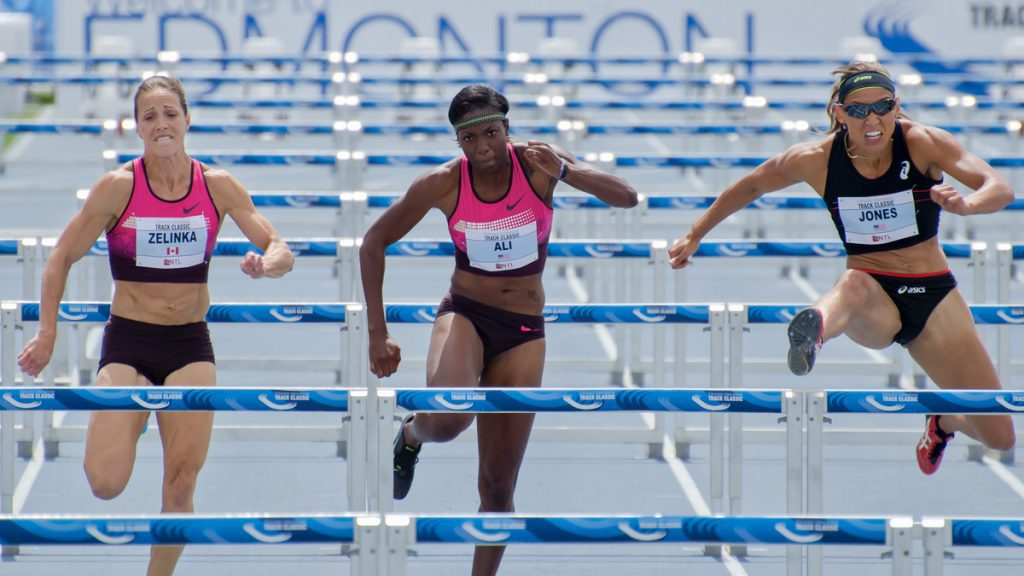 Picture of women competing for their country running hurdles - PPOC (Professional Photographers of Canada)