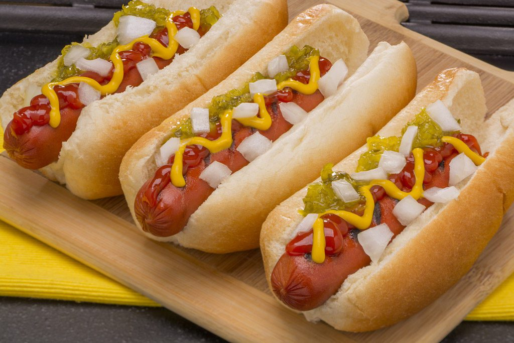 Circle K - Photo of three Hot dogs with mustard, ketchup, relish and onions