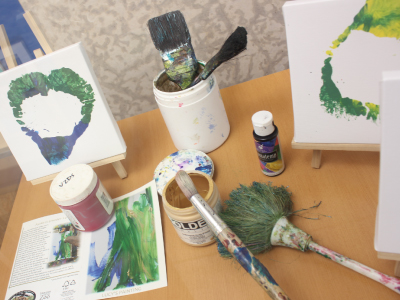 Photograph of the various paint brushes and paints that Lucy the Elephant uses to create her masterpieces
