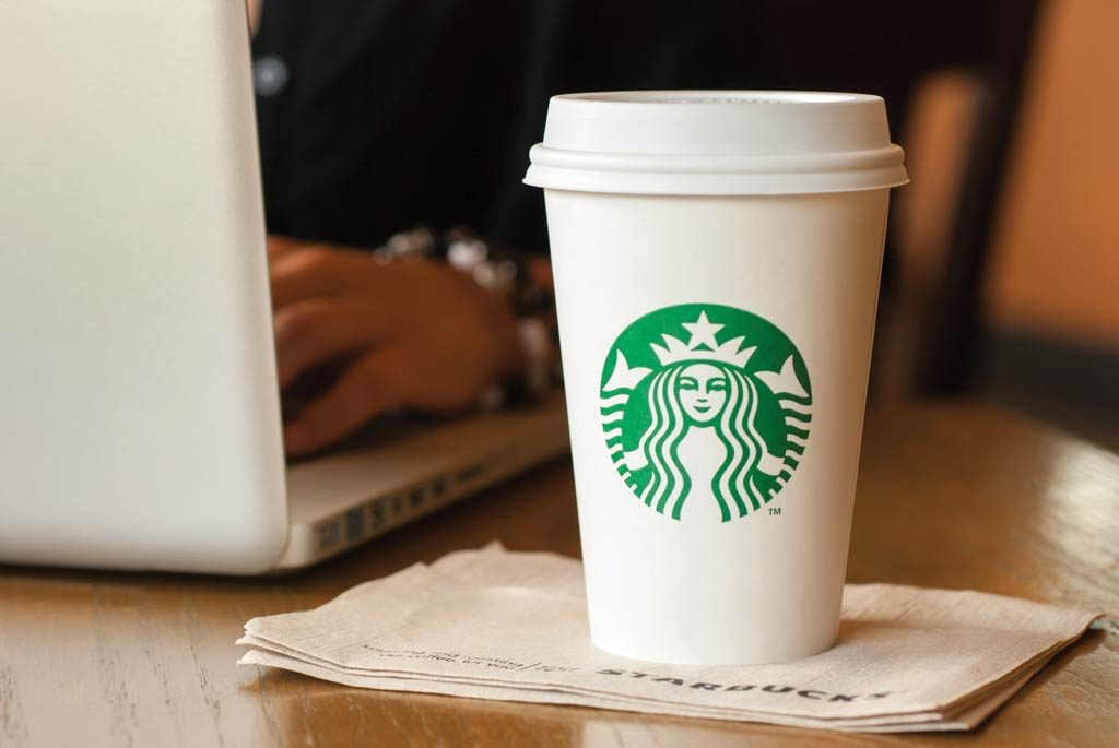 Photograph of customer working on laptop while enjoying a Starbucks coffee