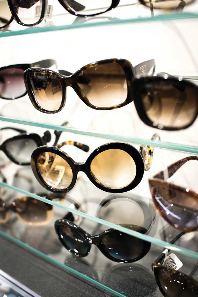 Photograph of various designer sunglasses on shelf