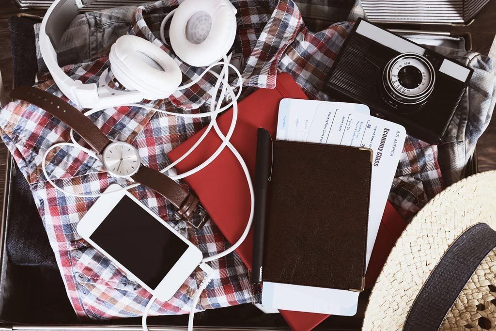 Photograph of headphones, watch, phone, boarding pass, camera ready to be packed for vacation